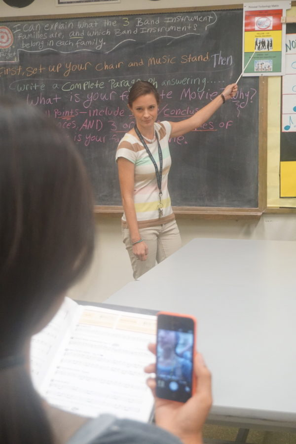 Blythe Emler, band teacher, reminds students about the new cell phone use procedure by pointing to the chart.