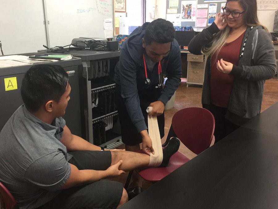 Students receive training on ankle wrapping in a mission to save Santa, before ending the class with food and friendship.